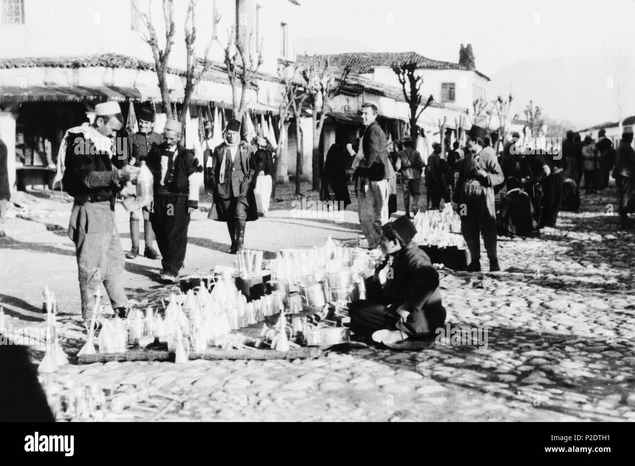 . Deutsch: Bazar im Zentrum von Tirana. Der Händler verkauf Blechgeschirr wie Trichter und Töpfe. 1923. Frank and Frances Carpenter. 63 Tirana Bazar - Stock Image