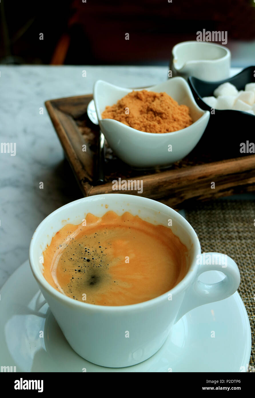 One Cup of Hot Americano Served on the Table with a Coffee Condiment Set - Stock Image