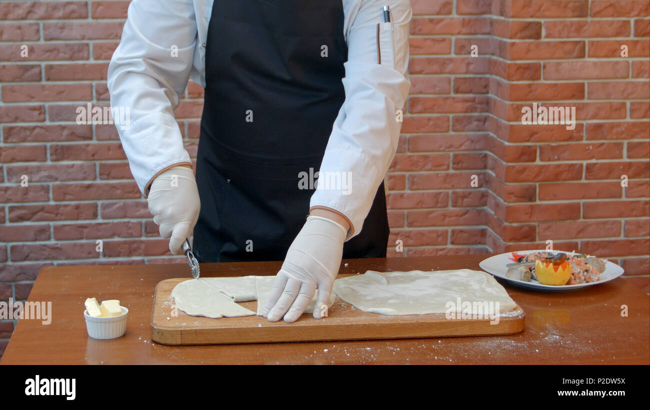 Chef hads slicing dough sheet with roller knife Stock Photo