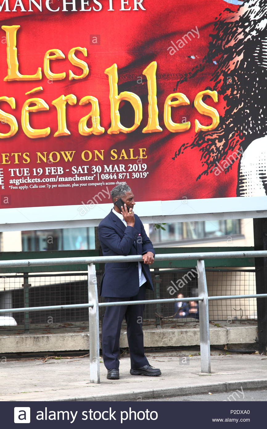 A man in uniform standing next to a Les Miserables advert using mobile phone at Manchester City Centre Uk Summer June 2018 - Stock Image