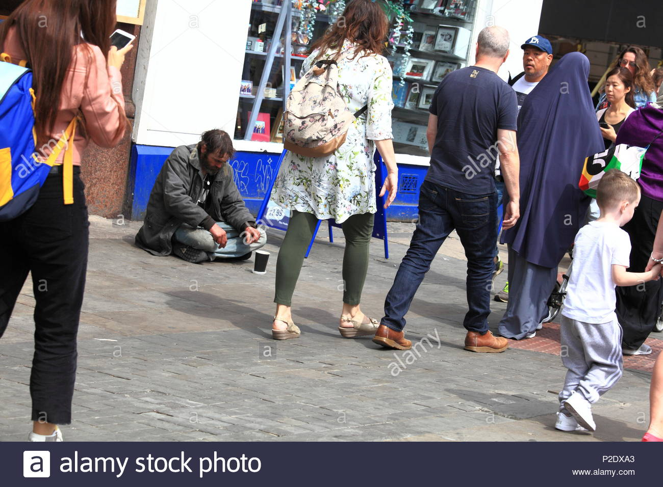 A beggar sits on the floor with cardboard cup and change as passers by look on at Manchester City Centre Uk Summer June 2018 - Stock Image