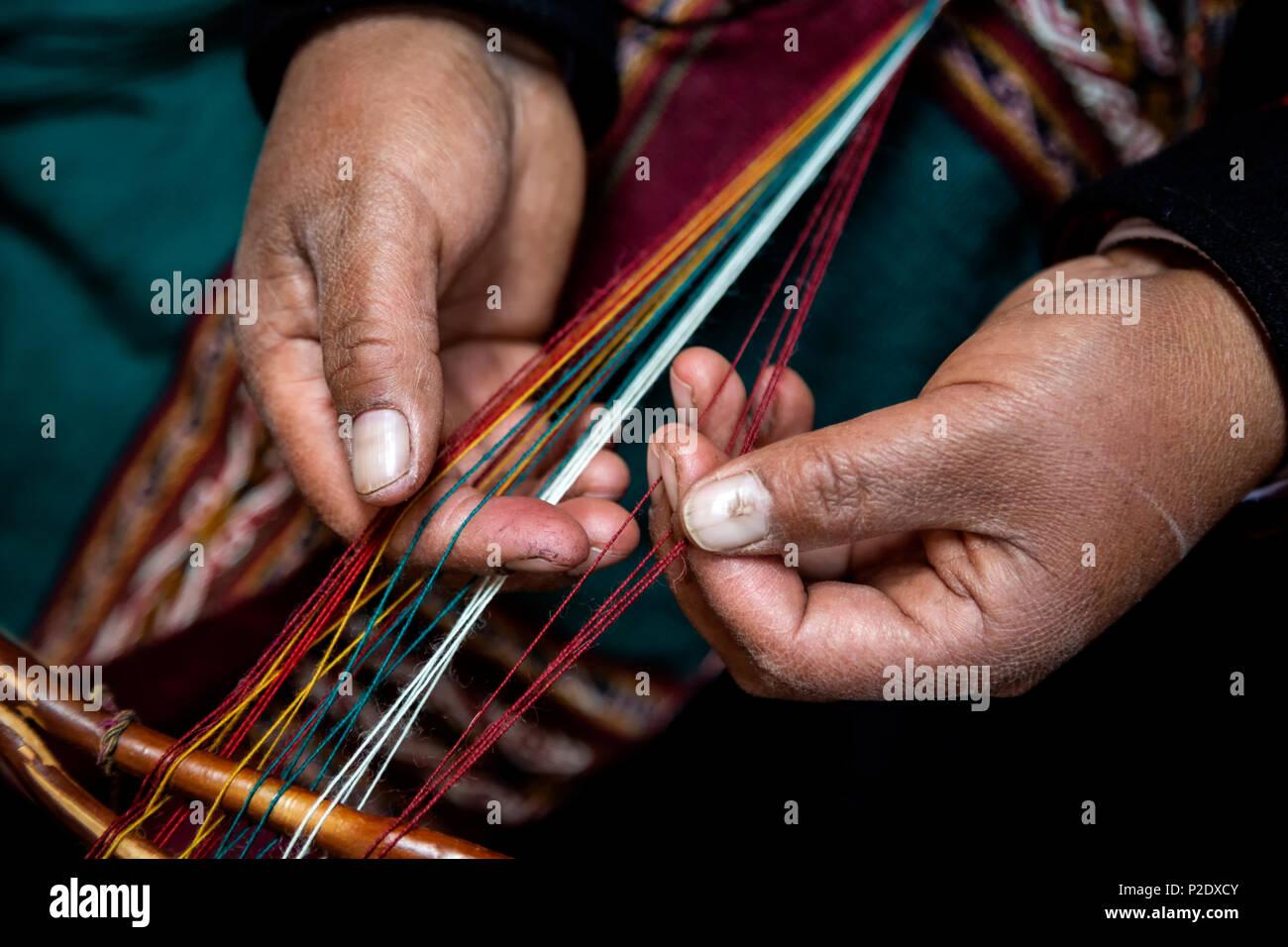 Hands of Quechua woman demonstrating weaving techniques, El Balcon del Inka, Chinchero, Cusco, Peru - Stock Image