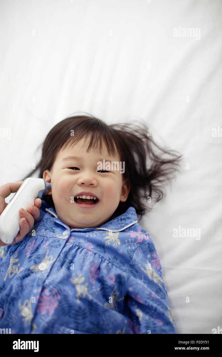 taking baby girl temperature using electric probe - Stock Image