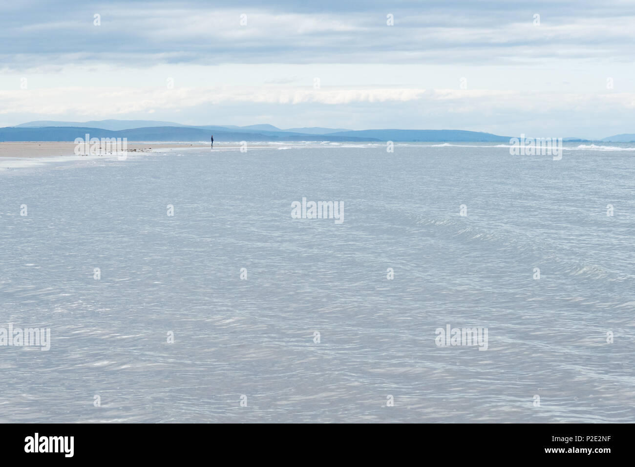 tiny male figure standing on empty beach looking out to sea, North Beach, Burghead Bay, Findhorn, The Moray Firth, Scotland, UK - Stock Image