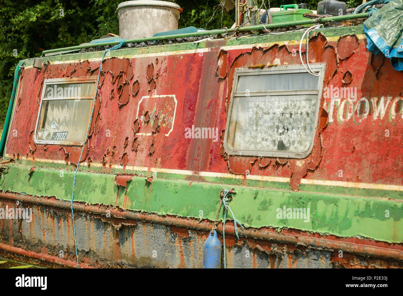 A rusting narrow boat in bad state of repair - Stock Image