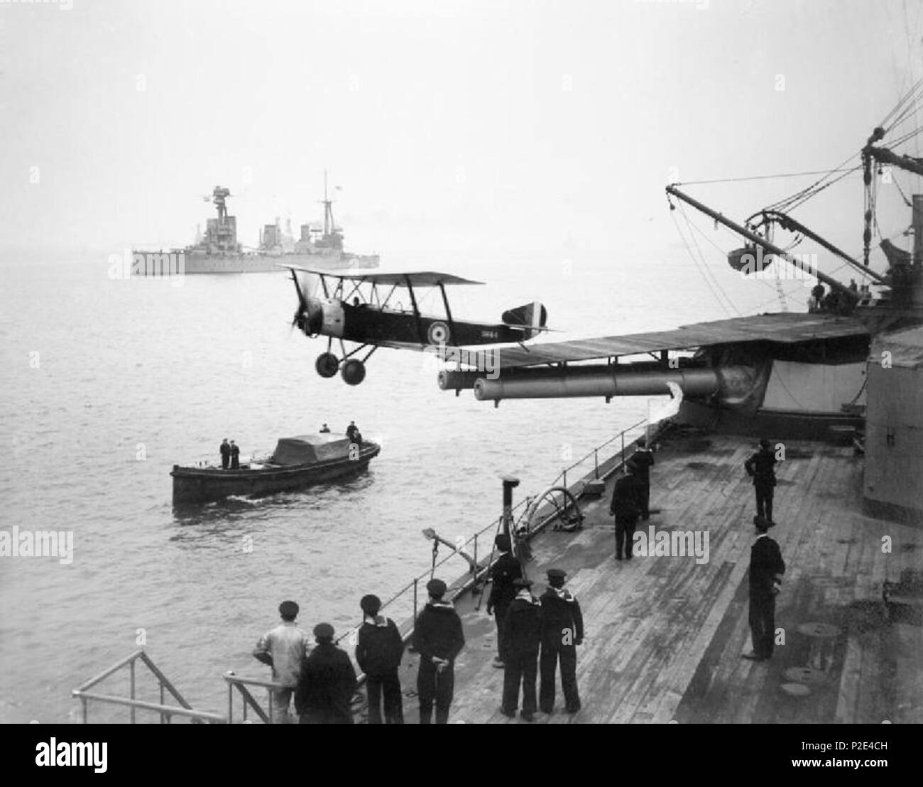 . A Sopwith 1 1/2 Strutter biplane aircraft taking off from a platform built on top of HMAS Australia's midships 'Q' turret. 1918. Associated News Agency 24 HMAS Australia launching aircraft 1918 - Stock Image