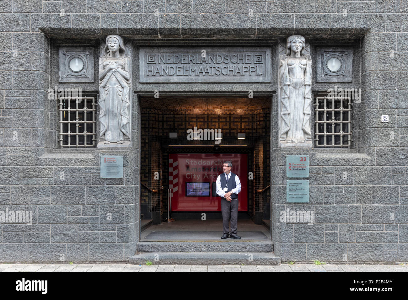 Security guard at doorway of former Netherlands Trading Society, now Amsterdam City Archives - Stock Image