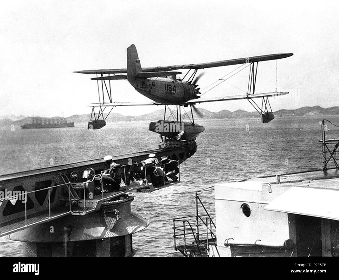 . A U.S. Navy Vought O2U-3 or O2U-4 Corsair floatplane of Scouting Squadron 11 is catapulted from the heavy cruiser USS Houston (CA-30), in Far Eastern waters, circa 1931-1932. The collier/seaplane tender USS Jason (AV-2) is in the left distance. circa 1932. USN 37 O2U Corsair is catapulted from USS Houston (CA-30) c1932 - Stock Image