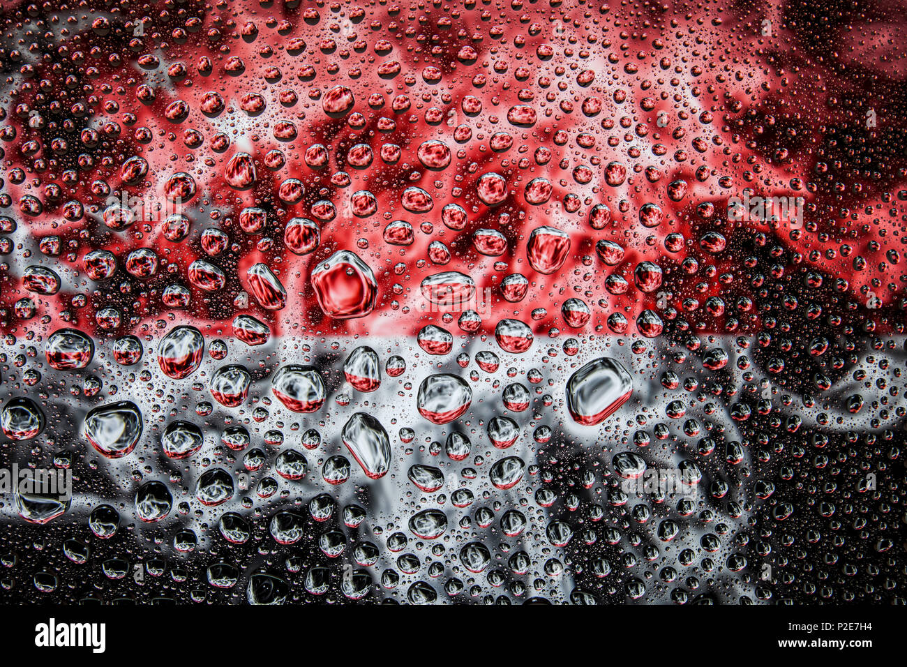 Close-up of a drop of water against a background of the national flag of  Singapore on an isolated background - Stock Image