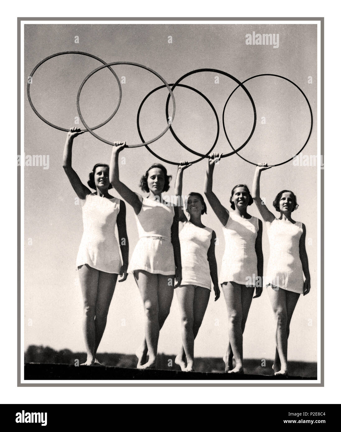 1936 Olympic Games, Berlin, Germany The Olympic Rings held aloft by five young sportswomen 1936 SUMMER OLYMPICS, BERLIN, real photo card showing dancers with the Olympic rings, BERLIN Olympic Stadium  AUGUST 13th 1936 Germany - Stock Image