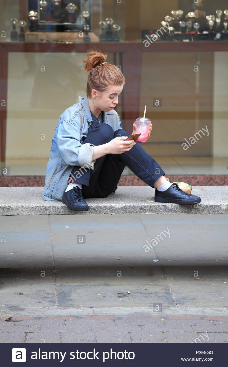 A young teenage girl sits on concrete stone seat drinking from plastic cup at Manchester City Centre Uk Summer June 2018 - Stock Image
