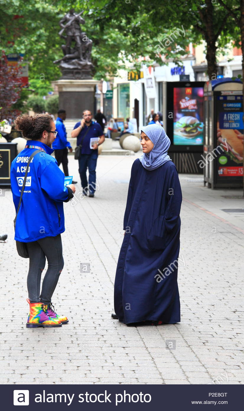 A street representative for PLAN INTERNATIONAL speaking with an asian lady at Manchester City Centre Uk Summer June 2018 - Stock Image