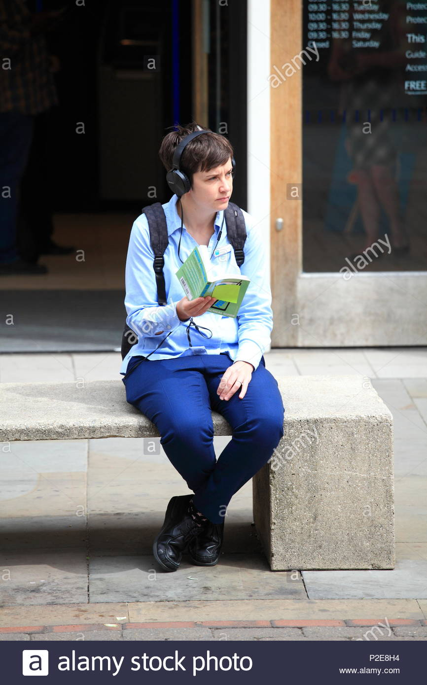 A male youth sitting on concrete stone bench reading a book about psychology at Manchester City Centre Uk Summer June 2018 - Stock Image