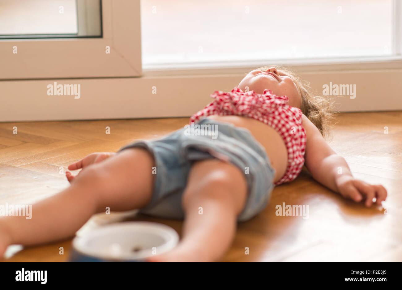 Beautiful blond child crying and shouting with tantrum laying on the floor at home. - Stock Image