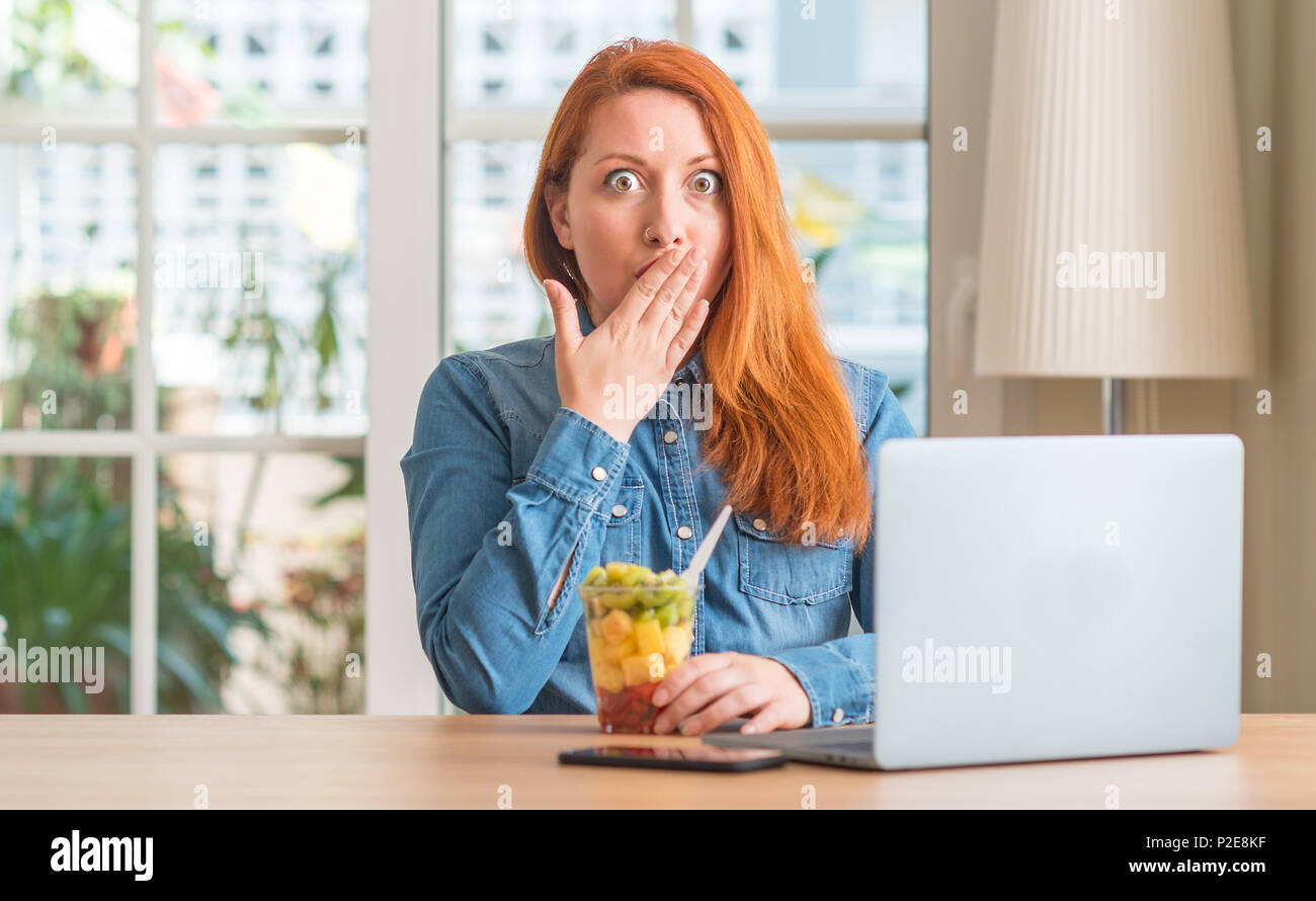Redhead woman using computer laptop eating fruit at home cover mouth with hand shocked with shame for mistake, expression of fear, scared in silence,  Stock Photo