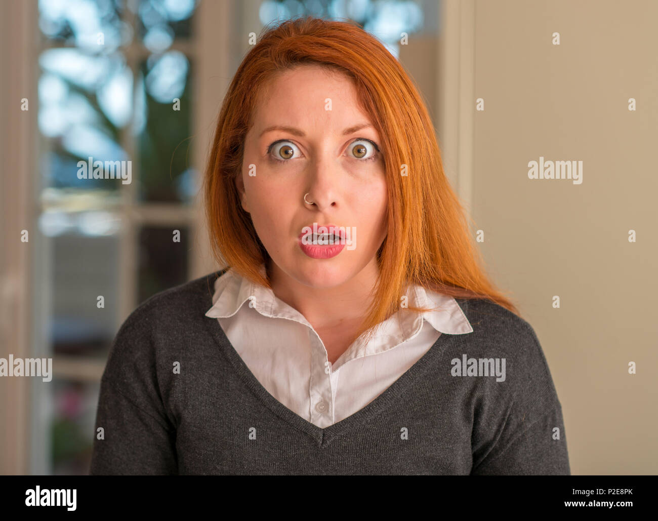 Redhead woman at home scared in shock with a surprise face, afraid and excited with fear expression Stock Photo