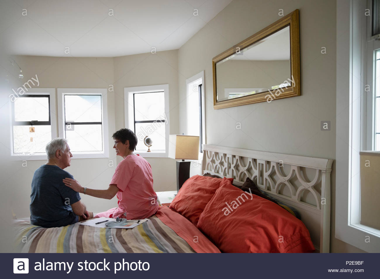 Home caregiver comforting senior man in bedroom - Stock Image