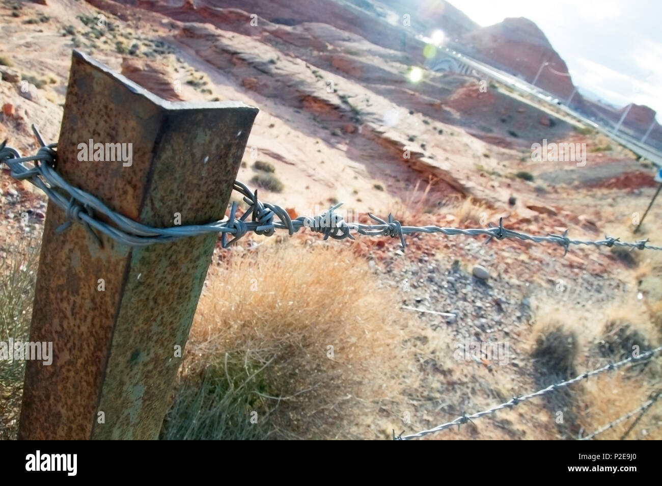 A barbed wire fence in the desert at sunset. - Stock Image