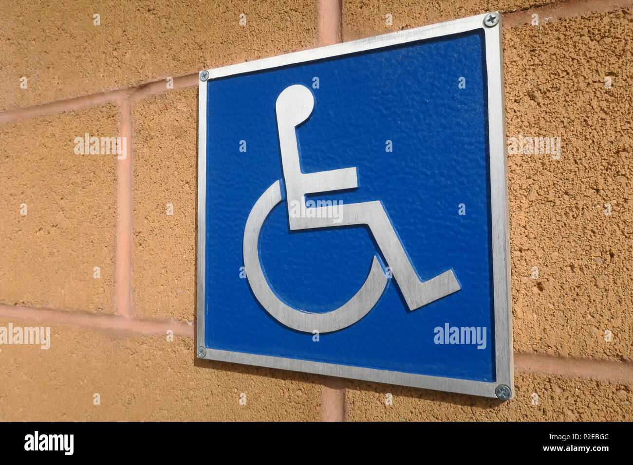 An angled handicap sign on a block wall. Stock Photo