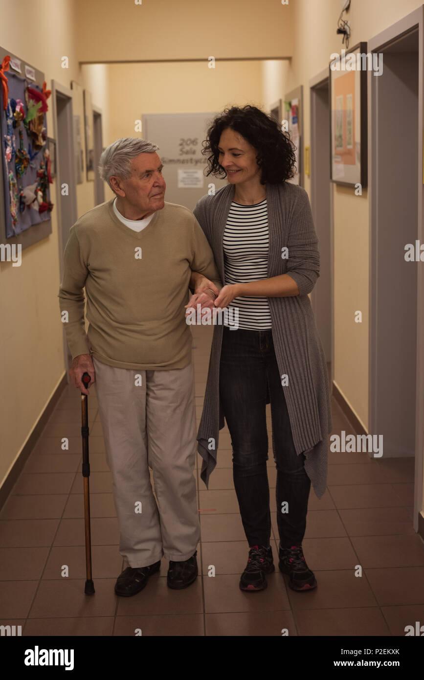Caretaker assisting senior man while walking in corridor - Stock Image