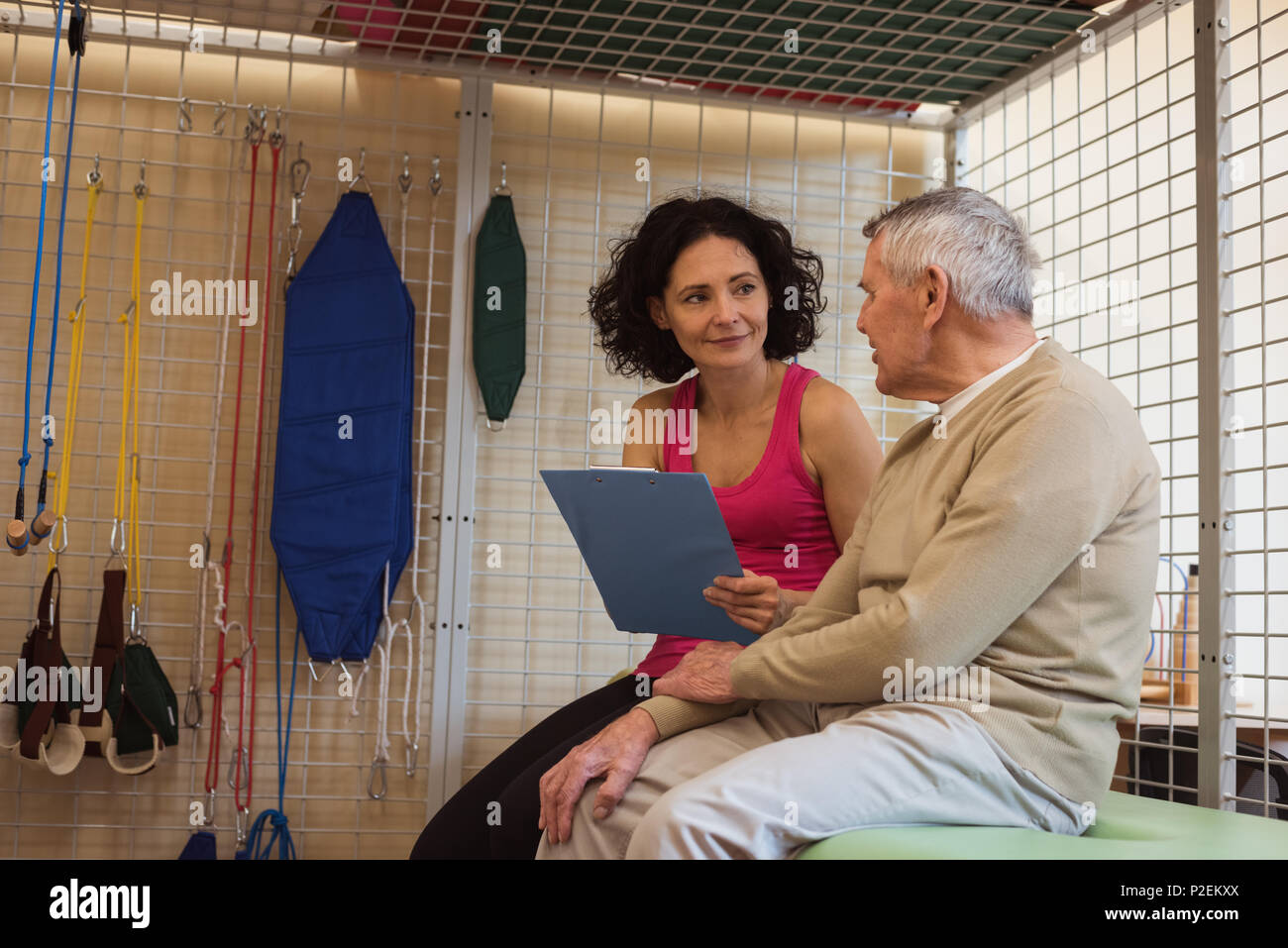 Female therapist discussing with senior man - Stock Image