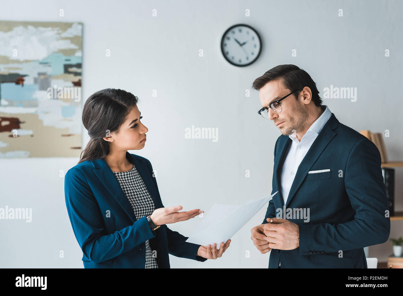 Colleagues in business suits arguing about contract details in modern office - Stock Image