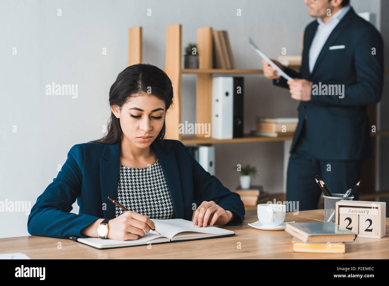 Colleagues in business suits studying papers in working office - Stock Image