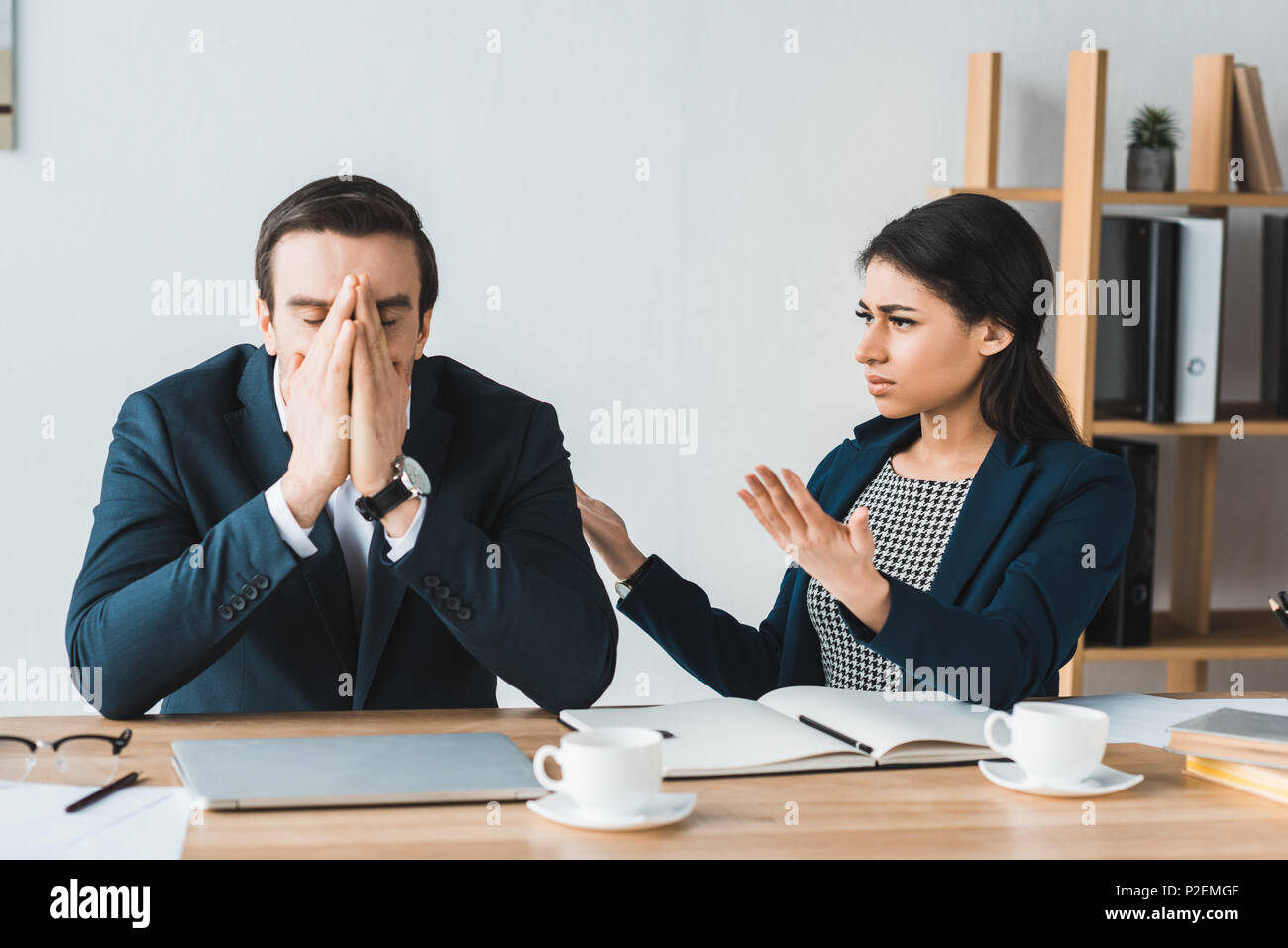 Colleagues in business suits arguing about project details in office - Stock Image