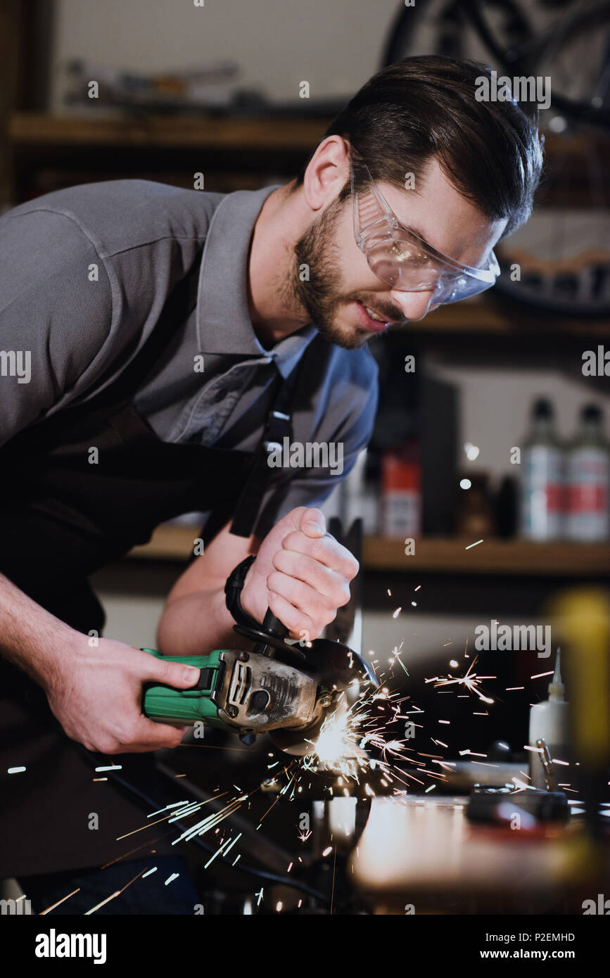 young man in protective goggles cutting metal with angle grinder in workshop - Stock Image