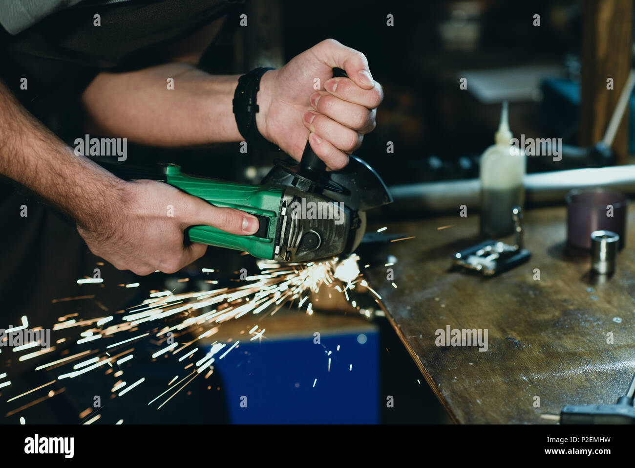 close-up partial view of man cutting metal with angle grinder in workshop - Stock Image
