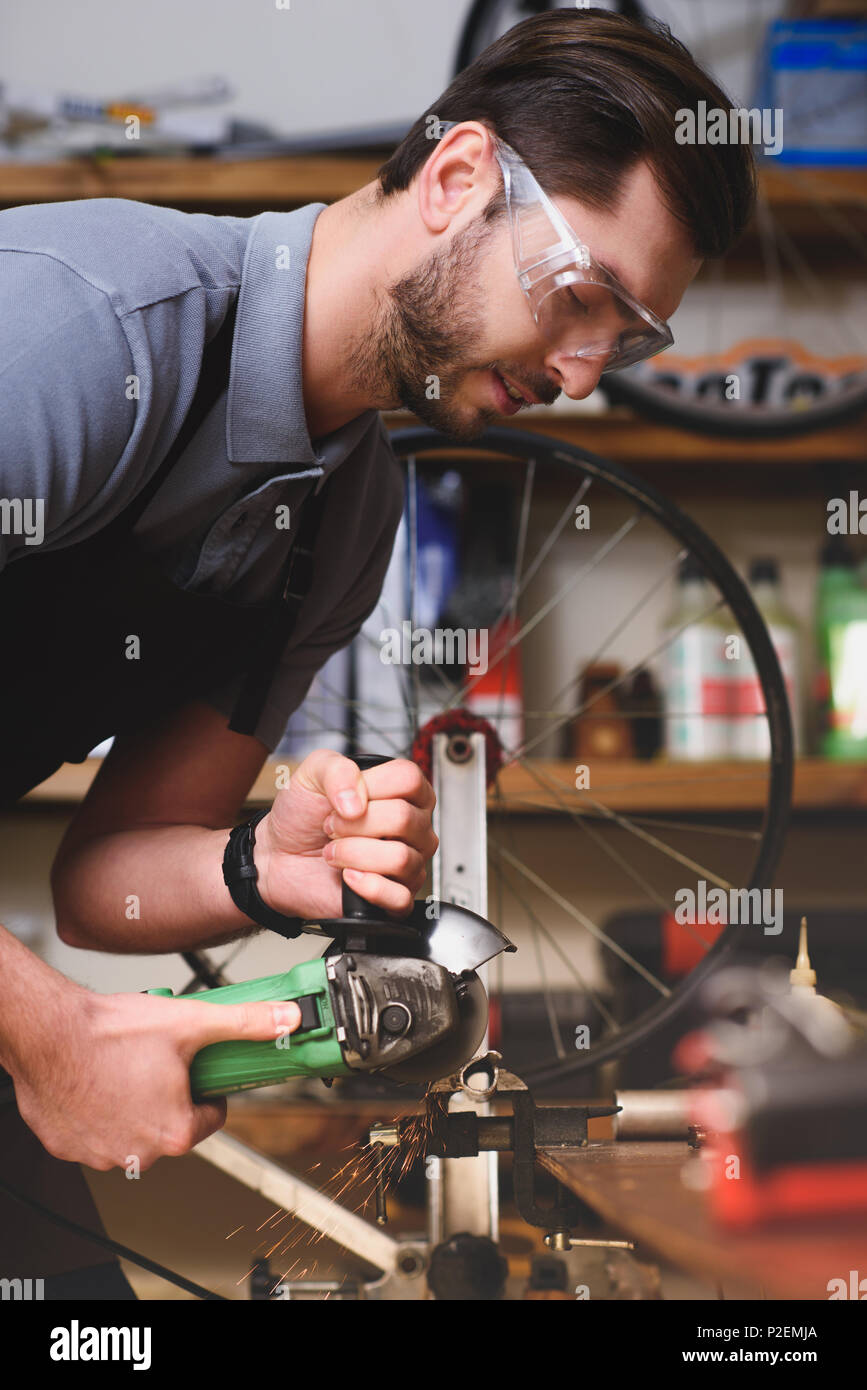 young man in protective goggles holding angle grinder in workshop - Stock Image