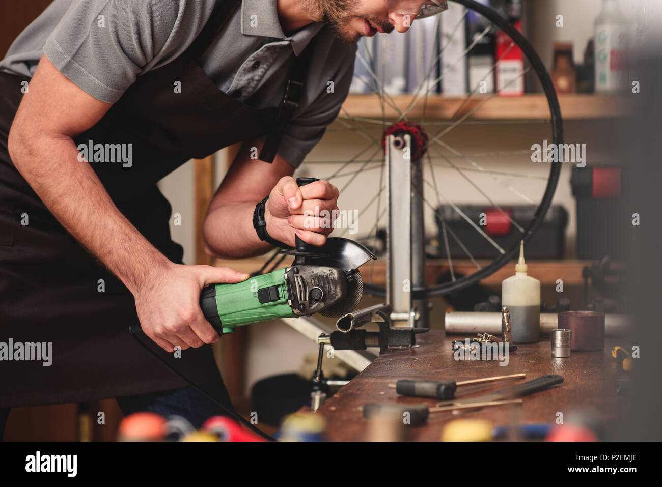 cropped shot of young worker cutting metal with angle grinder in workshop - Stock Image