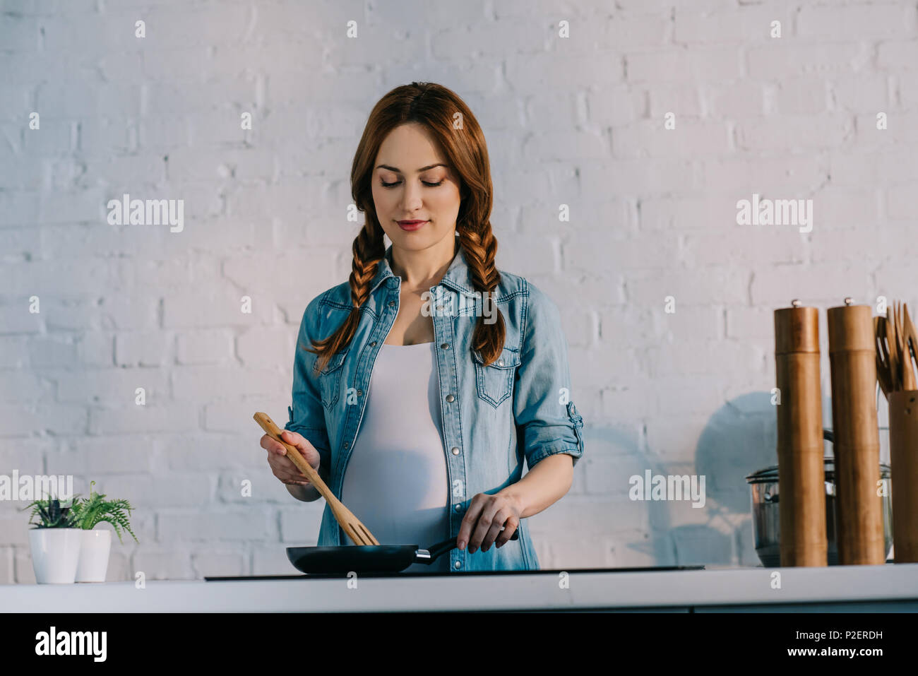 attractive pregnant woman cooking at electric stove at kitchen - Stock Image