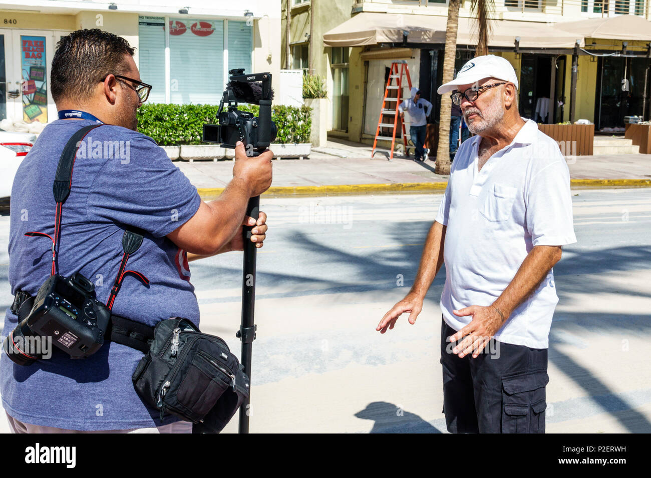 Florida Miami Beach Hispanic senior man reporter social media taping reporting interviewing camera blogger podcast interview interviewer - Stock Image