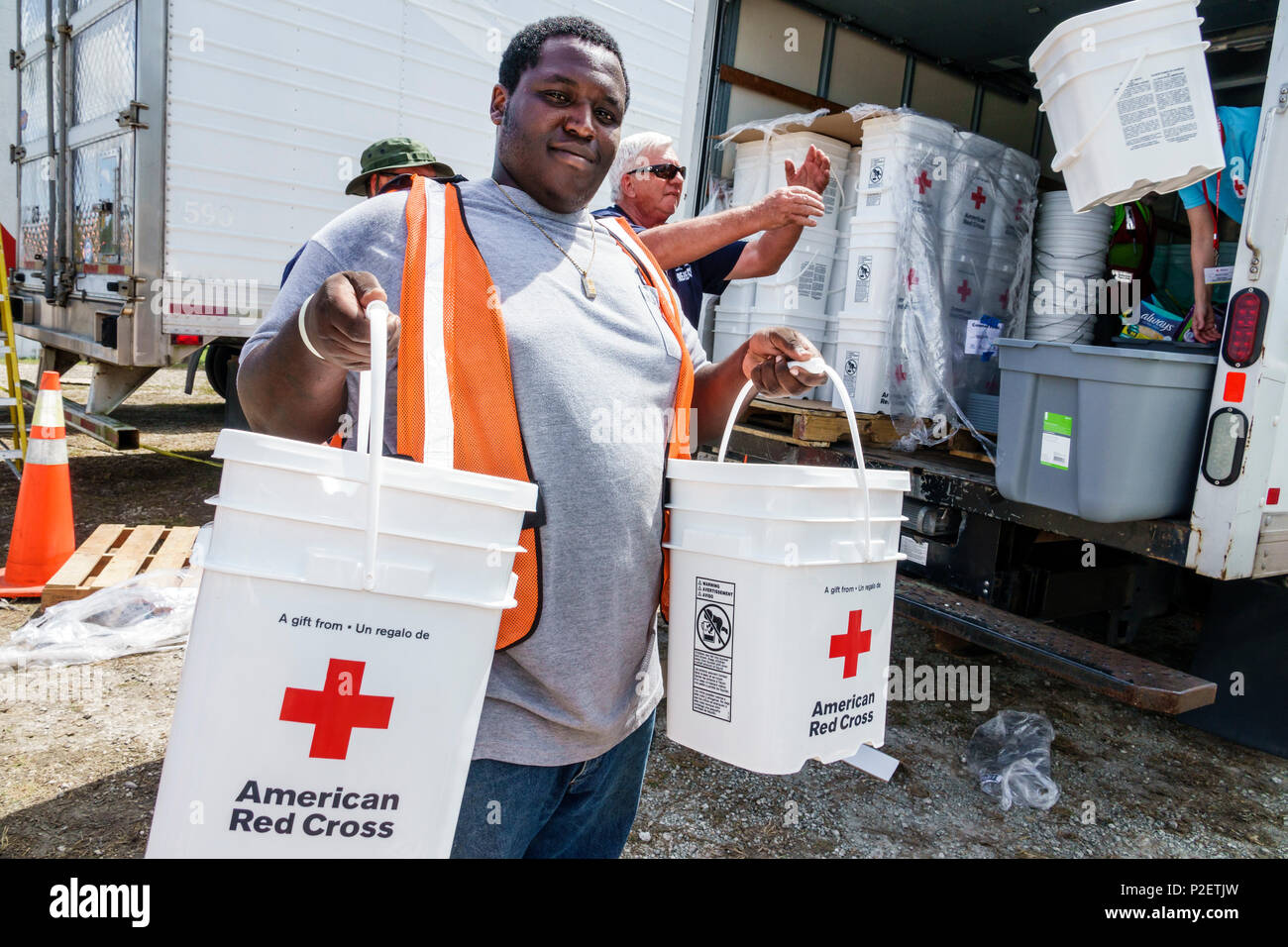 Florida Everglades City after Hurricane Irma emergency response recovery assistance distribution site Red Cross workers volunteer Black man unloading truck - Stock Image