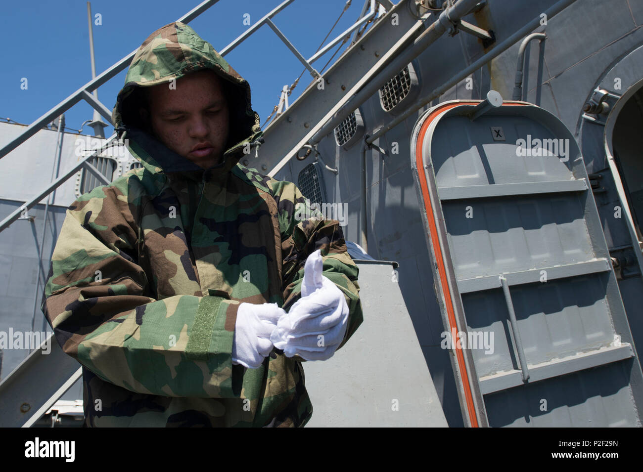 160905-N-ZE250-069   MEDITERRANEAN SEA (Sept. 05, 2016) - Seaman Christopher Longval dons a Joint Service Lightweight Integrated Suit Technology overgarment during a mission oriented protective posture exercise aboard USS Carney (DDG 64)  in the Mediterranean Sea Sept. 5, 2016. Carney, an Arleigh Burke-class guided-missile destroyer, forward-deployed to Rota, Spain, is conducting a routine patrol in the U.S. 6th fleet area of operations in support of U.S. national security interests in Europe. (U.S. Navy photo by Mass Communication Specialist 3rd Class Weston Jones/Released) - Stock Image