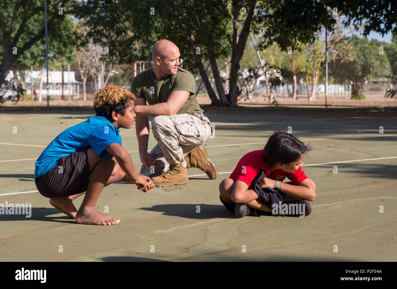 """U.S. Marine Corps Cpl. Landis Lied, an embarkation and logistics specialist assigned to Marine Fighter Attack Squadron (VMFA) 122, plays Red Red Bob, a version of the game """"tag"""", with students at MacFarlane Primary School Katherine, Northern Territory, Australia, Sept.1, 2016. Invited by the school every iteration of Southern Frontier, a three week unit level training conducted by U.S. Marines  at Royal Australian Air Force Base Tindal, Marines mentor, teach and provide role models to the students. With a student population of 92 percent indigenous, students are provided a consolidated educati - Stock Image"""