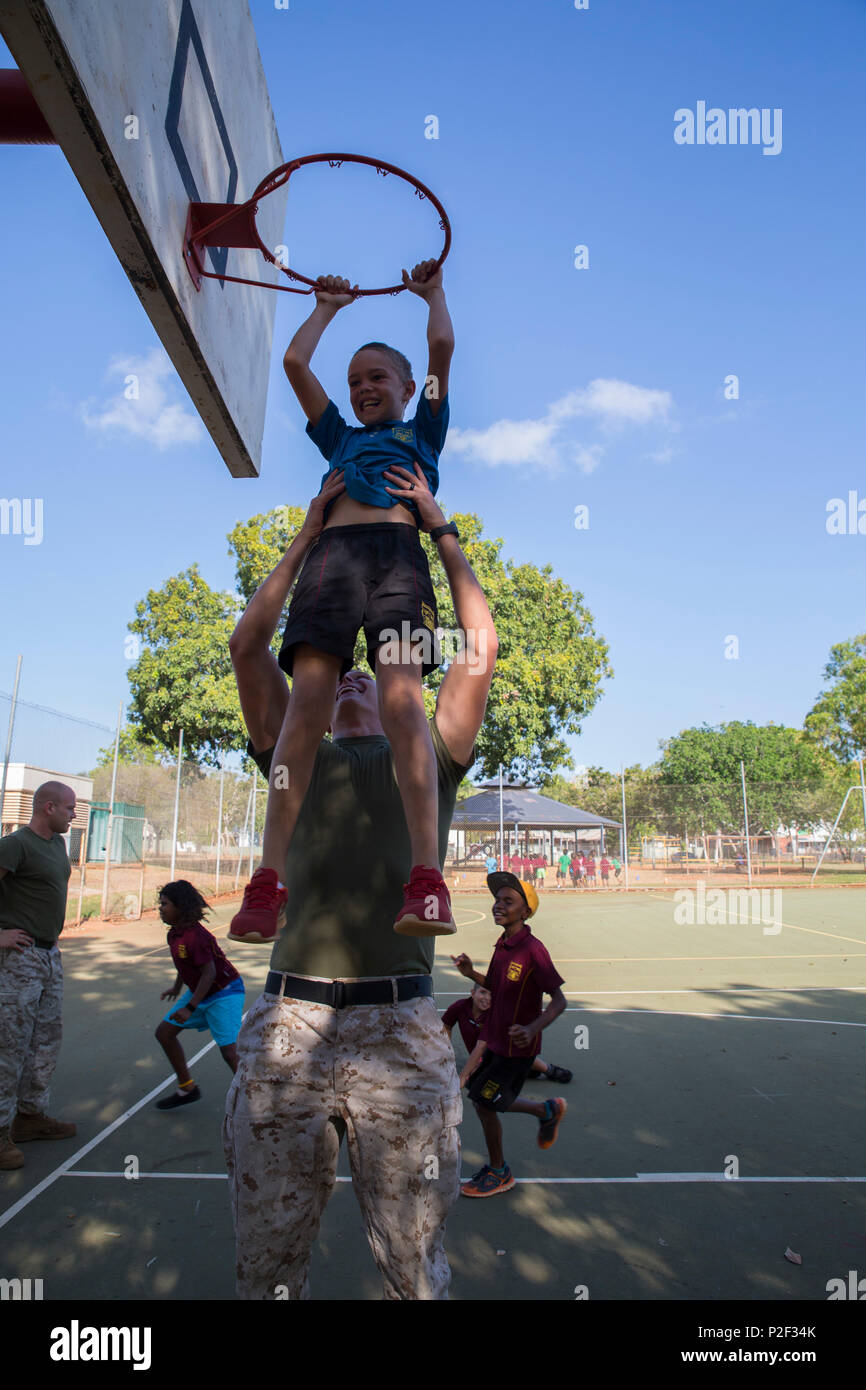 U.S. Marine Corps Cpl. Cody Braunscheidel, an aviation logistics information management systems specialist assigned to Marine Fighter Attack Squadron (VMFA) 122, lifts a student up at MacFarlane Primary School in Katherine, Northern Territory, Australia, Sept.1, 2016. Marines are invited to the school every iteration of Southern Frontier, a three week unit level training conducted by U.S. Marines at Royal Australian Air Force Base Tindal, to mentor, teach, and be role models to the students. MacFarlane Primary School also gives the students a consolidated education in literacy, numeracy, respe - Stock Image
