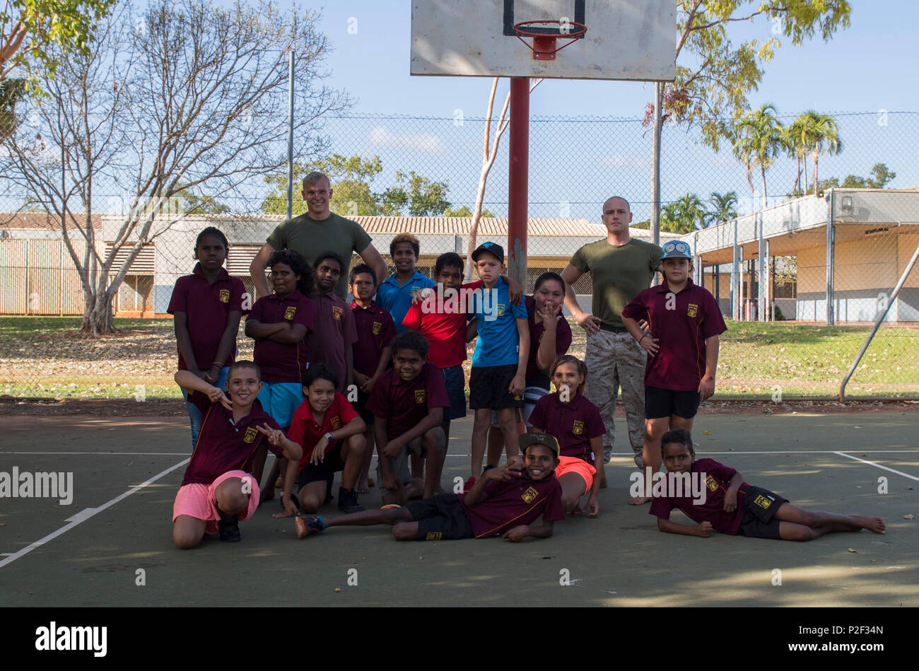 U.S. Marine Corps Cpl. Cody Braunscheidel, left, an aviation logistics information management systems specialist, and Cpl. Landis Lied, right, an embarkation and logistics specialist assigned to Marine Fighter Attack Squadron (VMFA) 122, pose with students from MacFarlane Primary School in Katherine, Northern Territory, Australia, Sept. 1, 2016. Marines are invited to mentor, teach and serve as role models to the students every iteration of Southern Frontier, a three week unit level training conducted by U.S. Marines at Royal Australian Air Force Base Tindal. With a population of 92 percent in - Stock Image