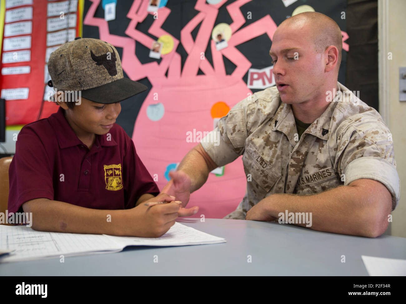 U.S. Marine Corps Cpl. Landis Lied, an embarkation and logistics specialist assigned to Marine Fighter Attack Squadron (VMFA) 122, helps a student with multiplication at MacFarlane Primary School in Katherine, Northern Territory, Australia, Sept. 1, 2016. Marines are invited to mentor and teach students every iteration of Southern Frontier, a three week unit level training conducted by U.S. Marines at Royal Australian Air Force Base Tindal. The primary school's student population is 92 percent indigenous and is very transient. Classes are designed to provide students structure and a consolidat - Stock Image