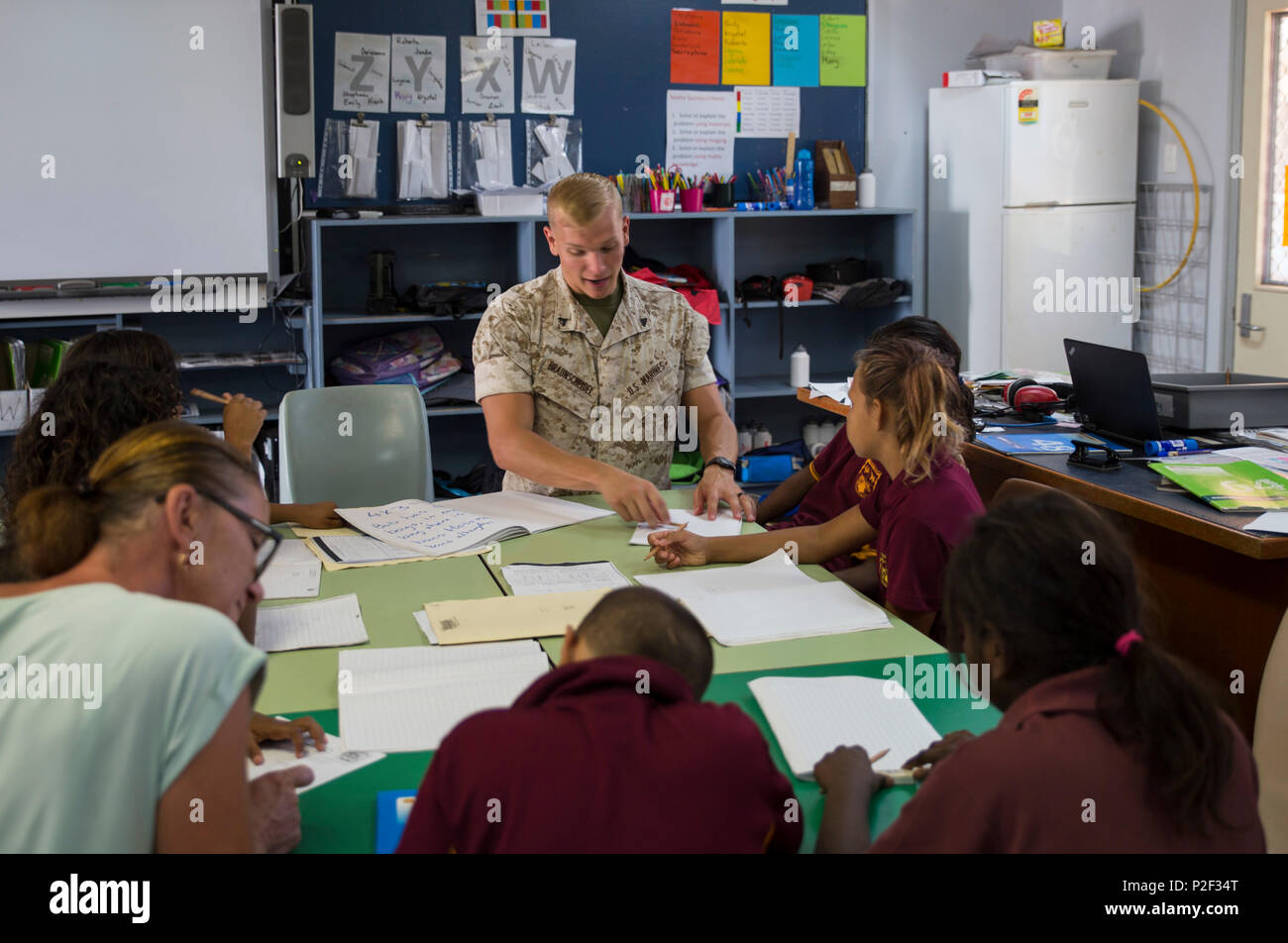 U.S. Marine Corps Cpl. Cody Braunscheidel, an aviation logistics information management systems specialist assigned to Marine Fighter Attack Squadron (VMFA) 122, explains multiplication to students at MacFarlane Primary School in Katherine, Northern Territory, Australia, Sept. 1, 2016. Marines are invited to mentor and teach students every iteration of Southern Frontier, a three week unit level training conducted by U.S. Marines at Royal Australian Air Force Base Tindal. The primary school's student population is 92 percent indigenous and is very transient. Classes are designed to provide stud - Stock Image