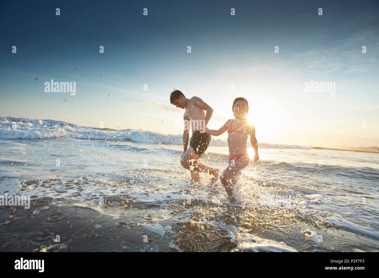 Sibling children on the beach of Canggu, low tide, Bali, Indonesia Stock Photo