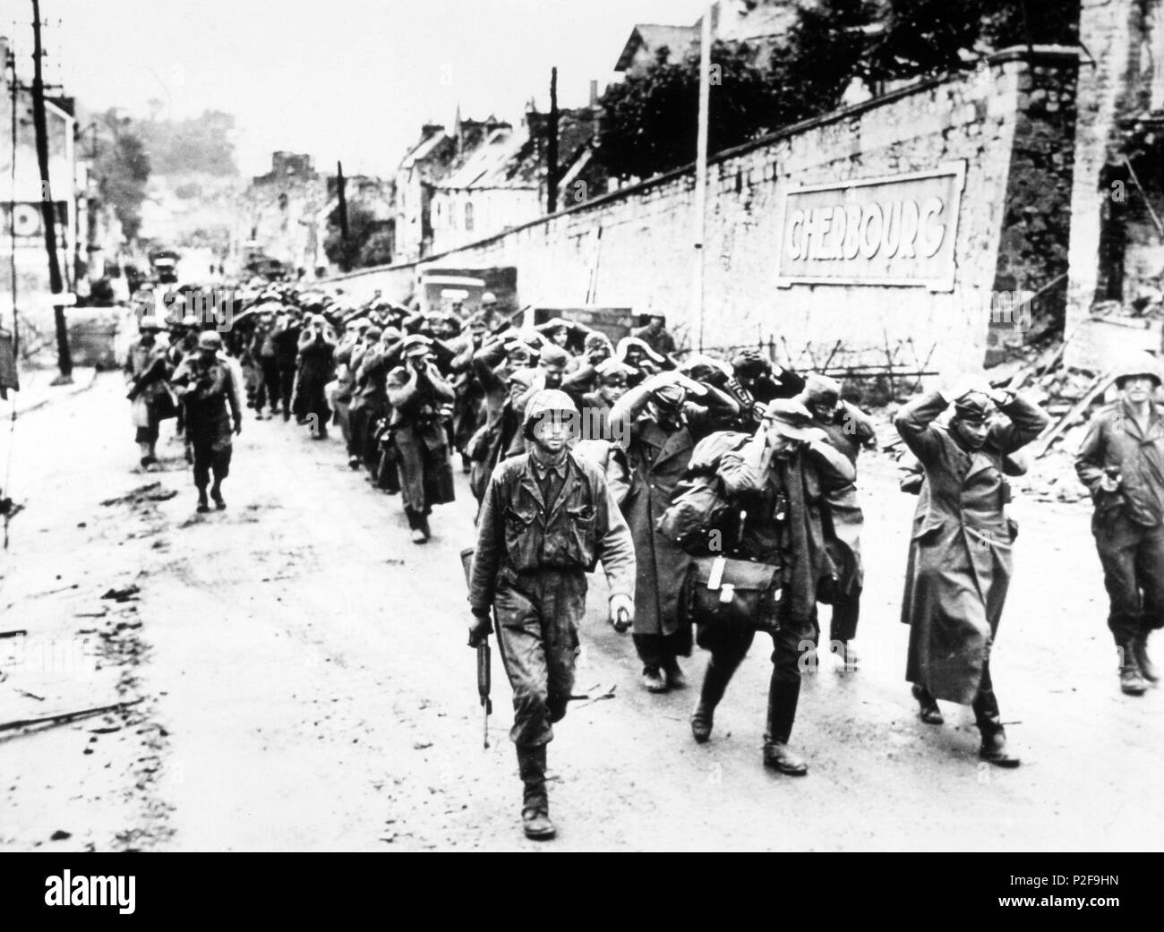 US GI's march German prisoners out of Cherbourg after the Battle of Cherbourg, June 1944. - Stock Image