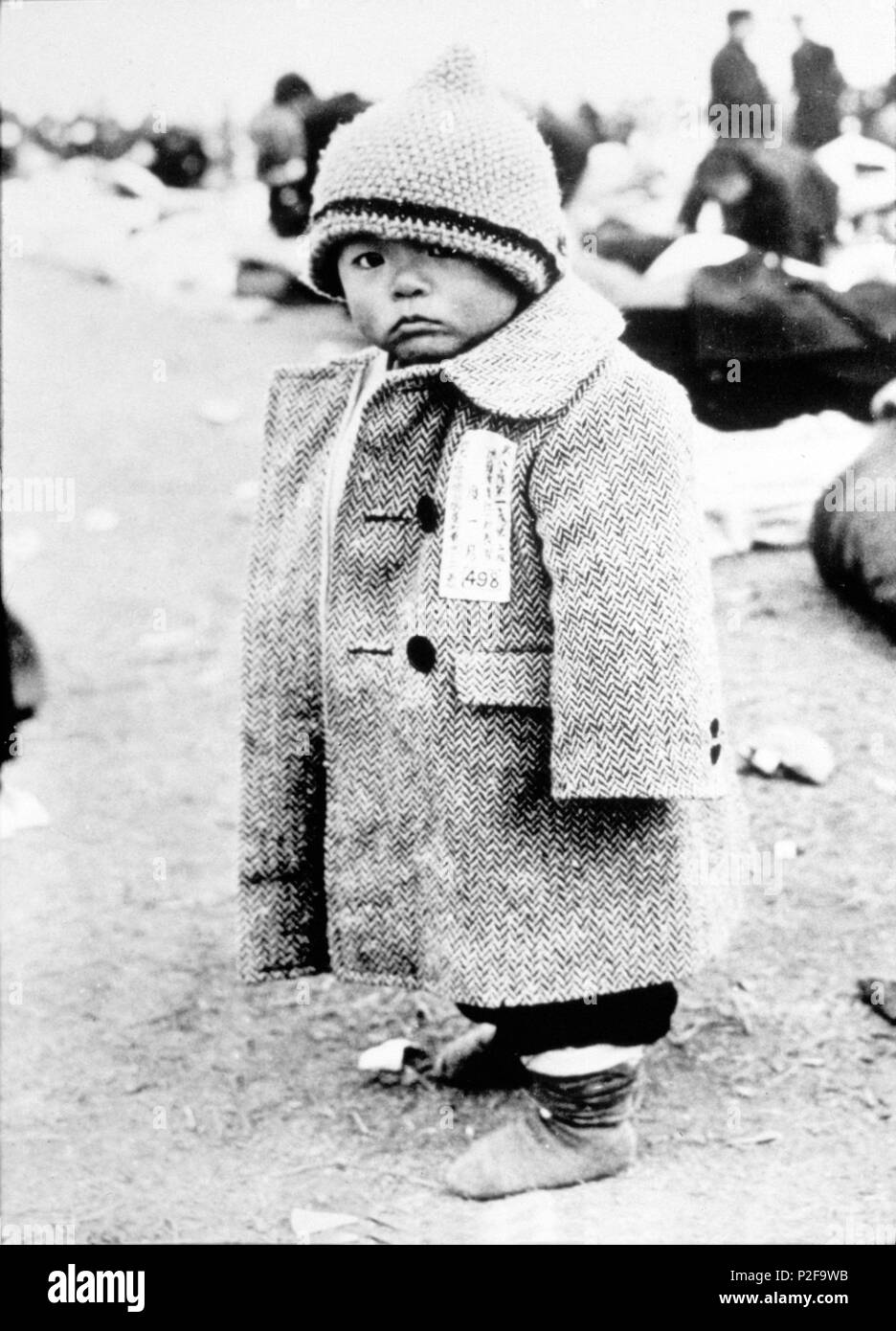 This youngster, clad in an oversize coat and bearing a label to prevent him becoming lost. His one of more than 4 milion Japanese transported by the US Navy from far Eastern ports and pacific islands. 1945. - Stock Image