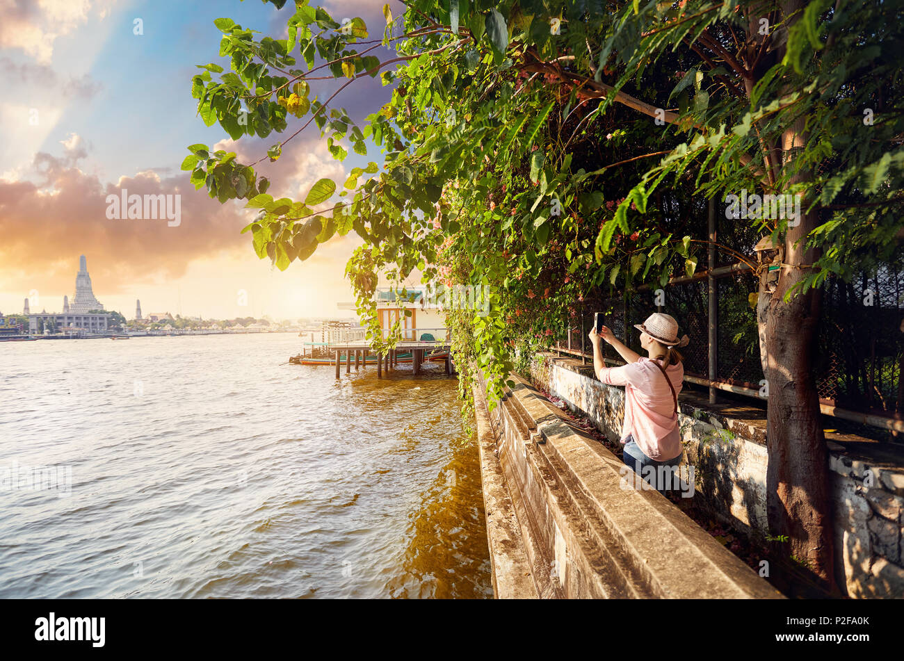Woman tourist taking a picture of Wat Arun with her phone at sunset in Bangkok, Thailand - Stock Image