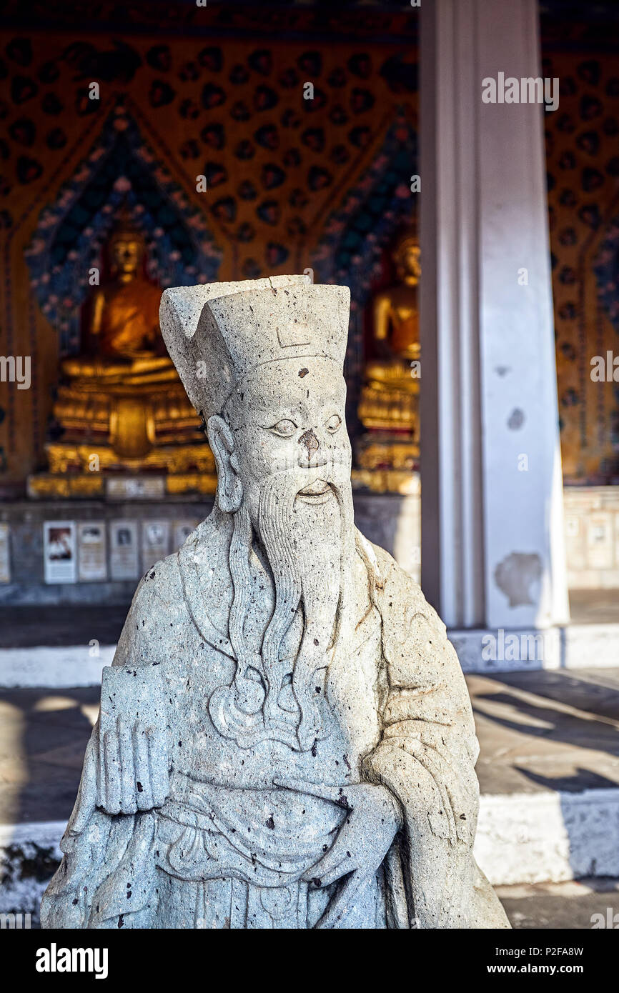 Stone statue of monk in Buddhist Temple Wat Arun in Bangkok, Thailand - Stock Image