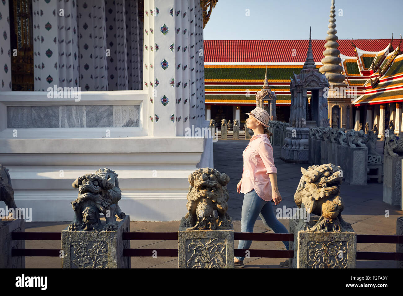 Beautiful tourist woman in hat and pink shirt walking in Wat Arun temple at sunset in Bangkok, Thailand - Stock Image