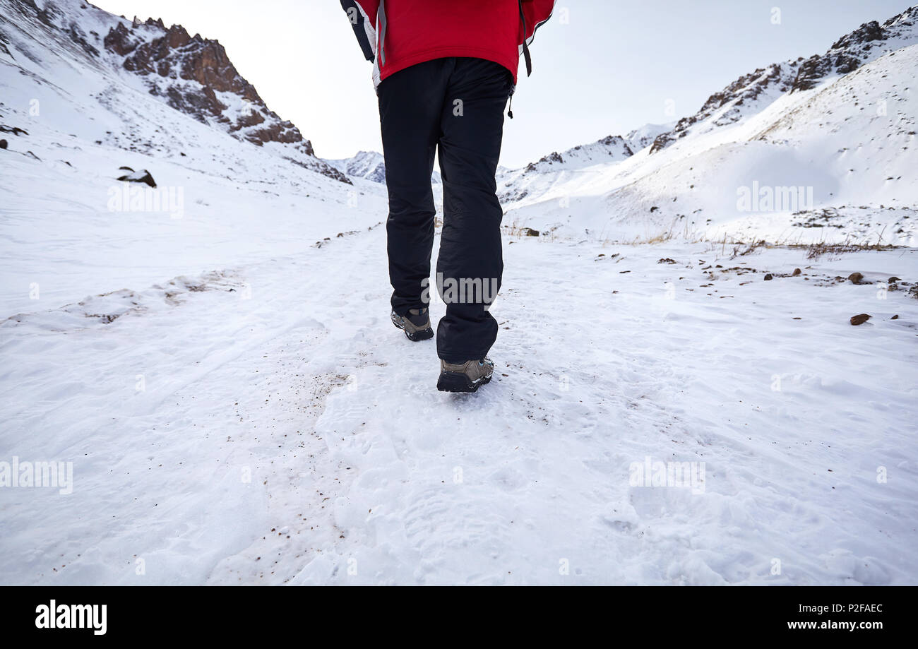 Hikers legs walking around snowy mountain. Freedom of trekking concept. - Stock Image