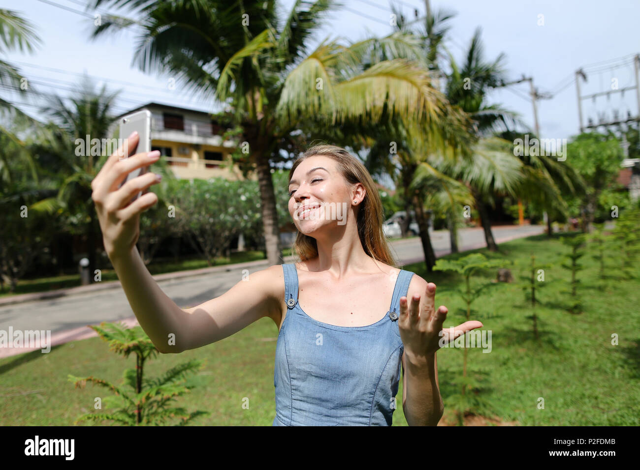 Young pretty girl making selfie by smarthone near palm trees in background. Stock Photo