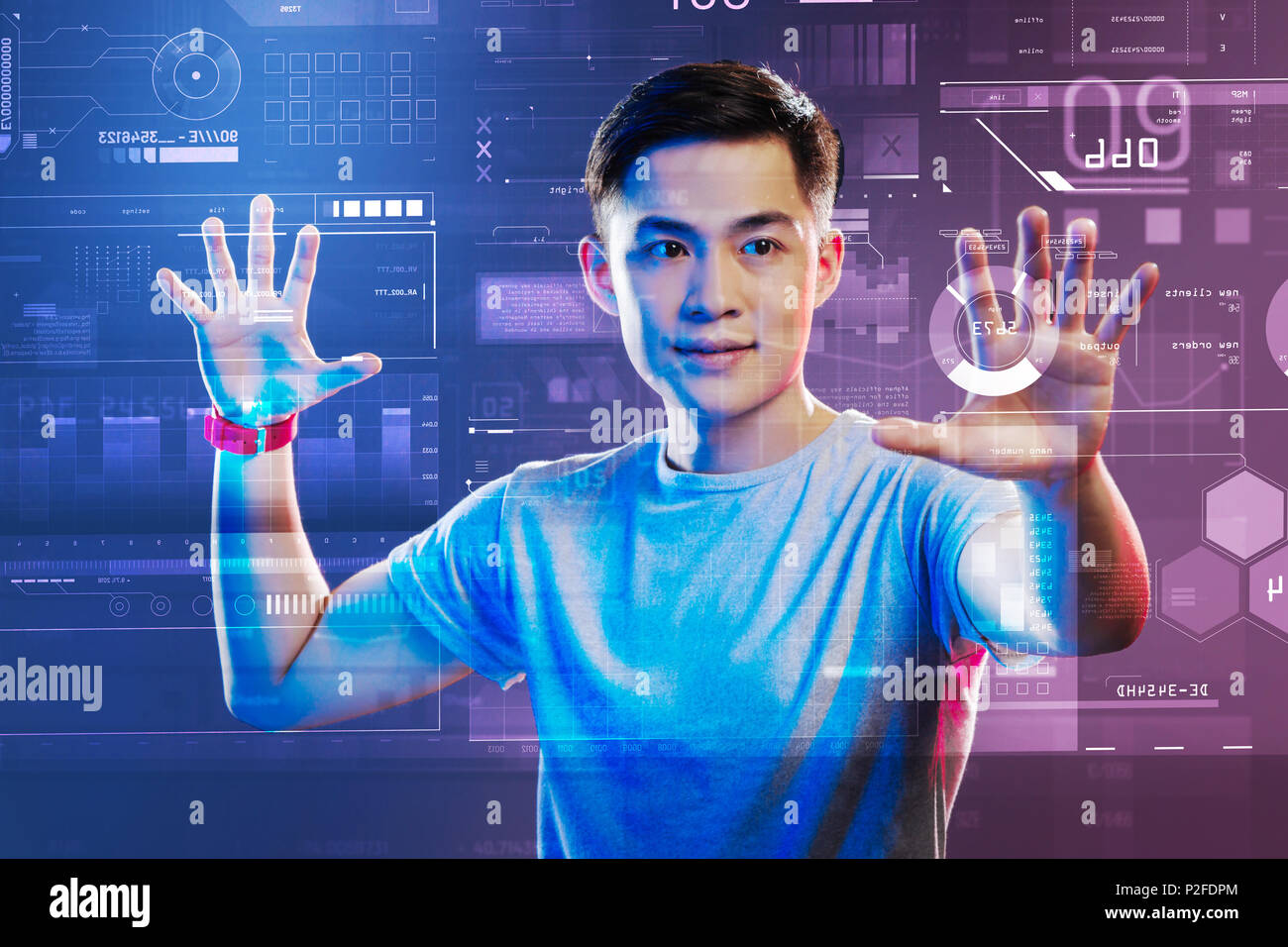 Professional web developer working with holographic images and looking impressed - Stock Image